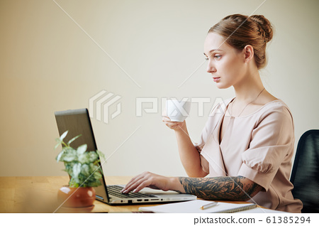Businesswoman Drinking Coffee While Working 61385294