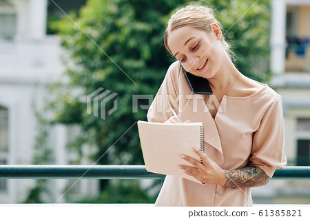Busy Woman Working Outdoors 61385821