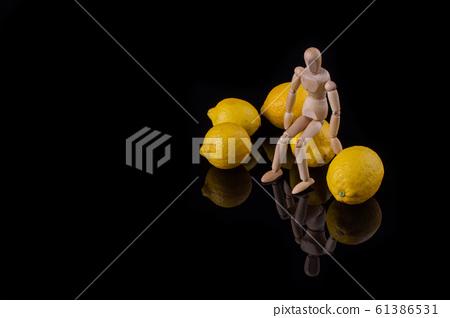 Wooden manikin sits among ripe lemons. 61386531
