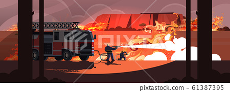 fire truck and firefighters extinguishing dangerous wildfire in australia fighting bush fire dry woods burning trees firefighting natural disaster concept intense orange flames horizontal 61387395