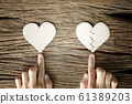 woman hand select between heart and broken heart paper cut on wooden background 61389203