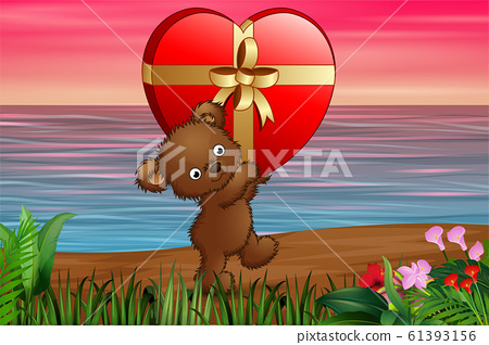 Teddy bear carrying big gift of red heart in the beach 61393156