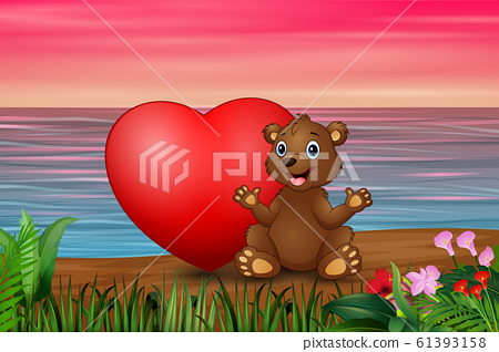 Funny baby bear sitting with red heart in the beach 61393158