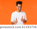 You can do it, say yes. Cheerful and confident young supportive african-american man in white t-shirt, wink and smile, showing thumbs-up gesture, rooting, encourage everything good, nice work 61393736