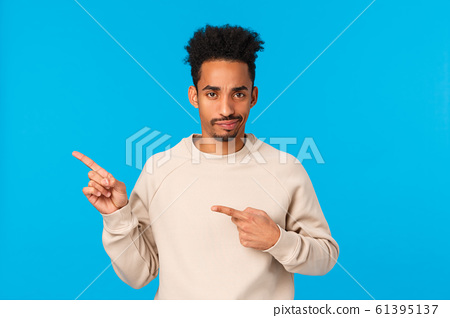Skeptical, serious-looking and disappointed african-american modern hipster guy with afro haircut, smirk and frowning unsatisfied, pointing left at bad product, stand judgemental blue background 61395137