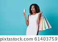 Excited woman showing credit card and shopping bag 61403759
