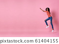Joyful young african woman in orange shirt jumping 61404155