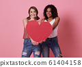 Lesbian couple standing and hand holding red heart 61404158