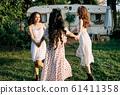 Happy beautiful women dancing outdoors on picnic 61411358