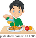 Little boy flowing maple syrup on pancakes with blueberries 61411785