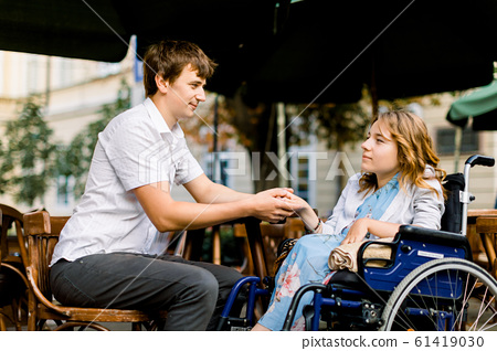 Pretty young woman on a wheelchair enjoying some good company on a date with her handsome man at a cafe outdoors in the city 61419030