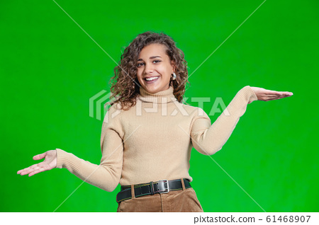 Photo of delighted young girl comparing two objects, weighting them in hands. 61468907