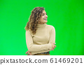 Hello everyone. Portrait of confident attractive and self-assured female looking to the side, smiling friendly over green background. 61469201
