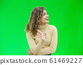 Hello everyone. Portrait of confident attractive and self-assured female waving hello, smiling friendly over green background. 61469227