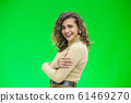 Beautiful woman with kinky hair in beige clothes, isolated on green, looking pleased. 61469270