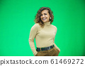 Glowing girl posing on green background, looking positive, smiling. 61469272