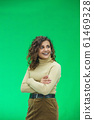 Portrait of gorgeous female model posing in white fashion clothes in studio over green background. 61469328