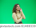 Portrait of gorgeous female model posing in white fashion clothes in studio over green background. 61469339