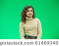 Beautiful woman with kinky hair in beige clothes, isolated on green, looking pleased. 61469340