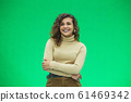 Portrait of a beautiful friendly african american woman with curly hairstyle and lovely smile isolated on a green background, her hands folded. 61469342