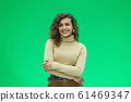Portrait of a beautiful friendly african american woman with curly hairstyle and lovely smile isolated on a green background, her hands folded. 61469347