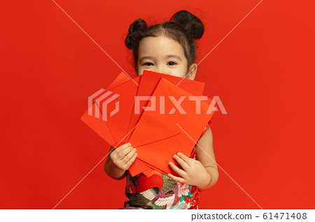 Happy Chinese New Year. Asian little girl portrait isolated on red background 61471408
