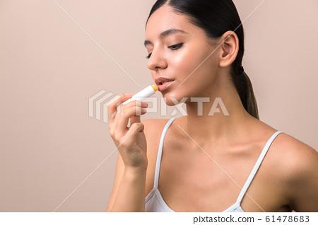 lips care and protection. woman applying balm on lips 61478683