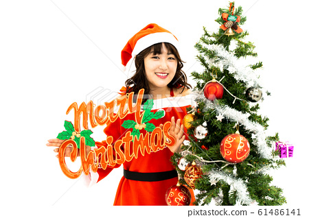 Woman in santa dress with christmas tree 61486141