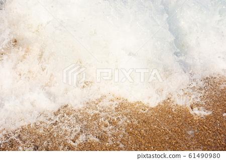 sea waves splash foam on the sunny beach 61490980