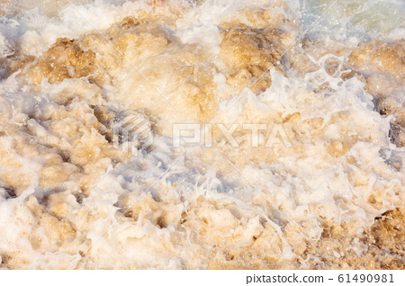 sea waves splash foam on the sunny beach 61490981