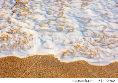 sea waves splash foam on the sunny beach 61490982