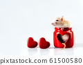 A light beige rat sitting in a red candlestick with a heart-shaped window 61500580