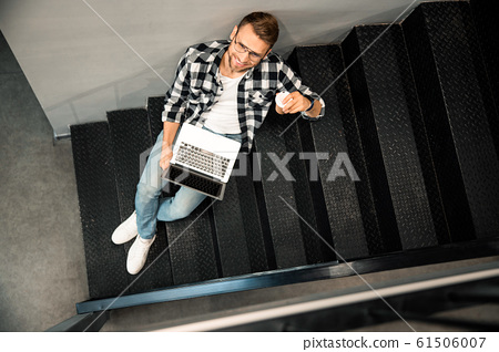Happy young man looking up while working with laptop 61506007