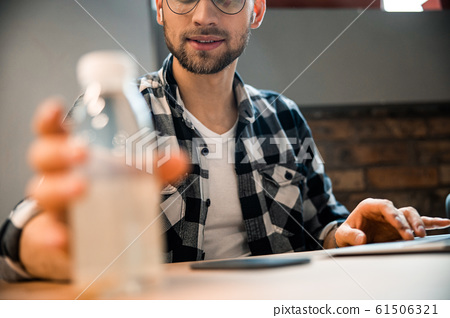 Smiling male freelancer is looking on bottle 61506321