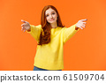 Girl asking come here to give cheer-up hug. Cute and touched tender redhead woman in yellow sweater, extend arms,stretch hands forward for cuddle, embrace friend, smiling lovely, orange background 61509704