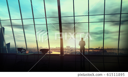 Businessman in front of a panoramic window overlooking the cityscape. 61511895