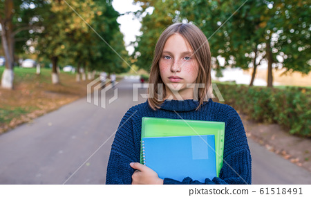 Sad and upset. A teenager girl of 12-15 years old, in summer in city, is holding notebooks and textbooks in her hands. Free space for copy text. The concept parenting thoughts of adolescents. 61518491