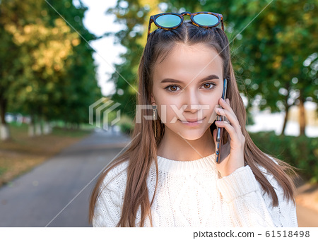 Teenager girl 12-15 years old, autumn day, portrait on street, phoning, in summer in park. Listens to voice message. Casual clothes, knitted white sweater. Call to parents. The concept of parenting. 61518498
