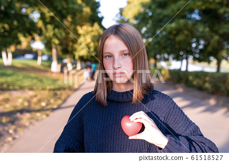 A teenager girl of 12-15 years old, in the summer in the city, holds a toy heart in her hand, concept gift love parenting help and support. Knitted warm sweater. 61518527