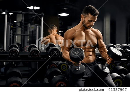 Male bodybuilder holding dumbbells on thighs. 61527967