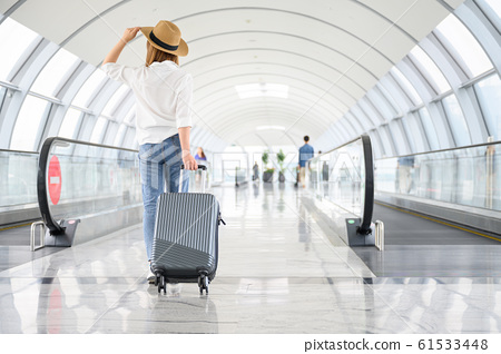 A woman with hand luggage walking in airport 61533448