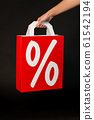 hand holding red shopping bag with percent sign 61542194