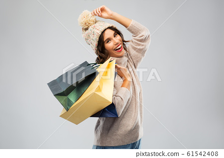 young woman in winter hat with shopping bags 61542408
