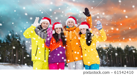 happy friends in santa hats and ski suits outdoors 61542410