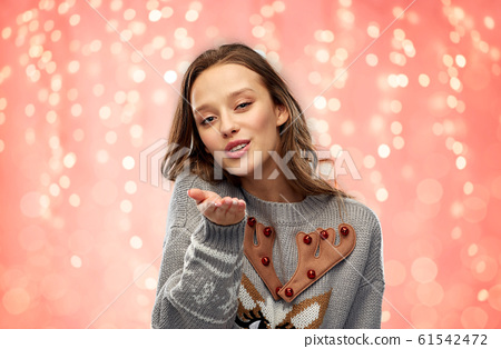 woman in ugly christmas sweater sending air kiss 61542472