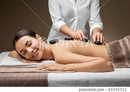 beautiful woman having hot stone massage at spa 61543322