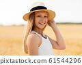 portrait of girl in straw hat on field in summer 61544296
