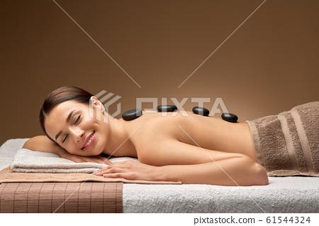 smiling woman having hot stone massage at spa 61544324