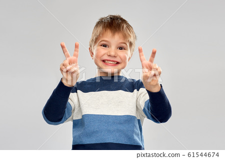 little boy in striped pullover showing peace 61544674