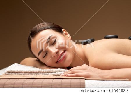 smiling woman having hot stone massage at spa 61544829